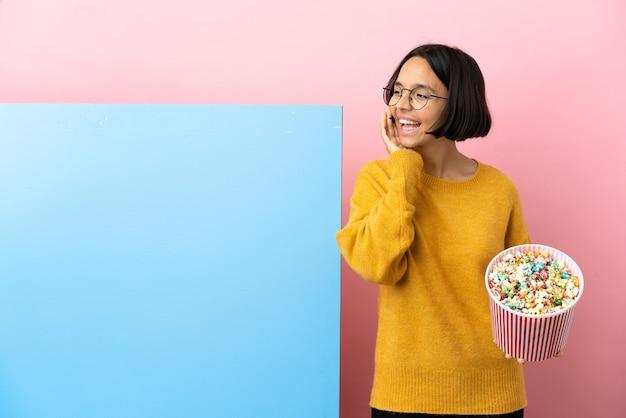 Молодая женщина смешанной расы, держащая попкорн с большим баннером на изолированном фоне, кричит с широко открытым ртом