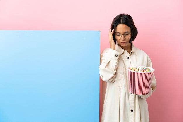 Молодая женщина смешанной расы, держащая попкорн с большим баннером на изолированном фоне с головной болью