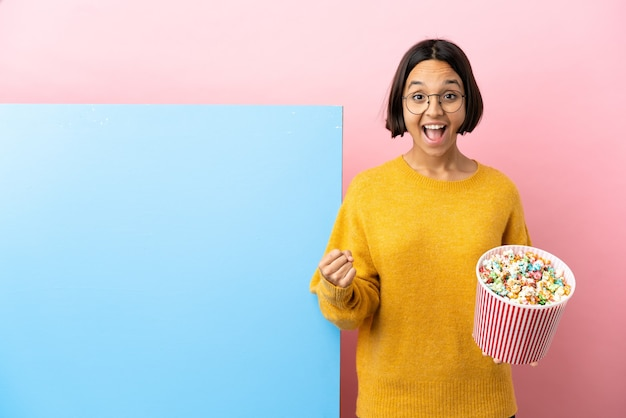 Young mixed race woman holding popcorns with a big banner isolated background celebrating a victory in winner position