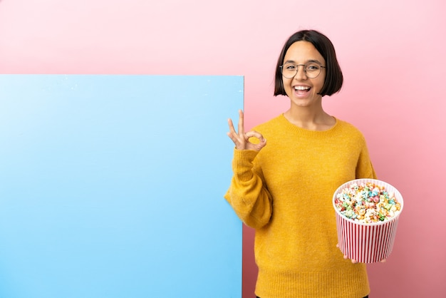 Young mixed race woman holding popcorns with a big banner over isolated background showing ok sign with two hands
