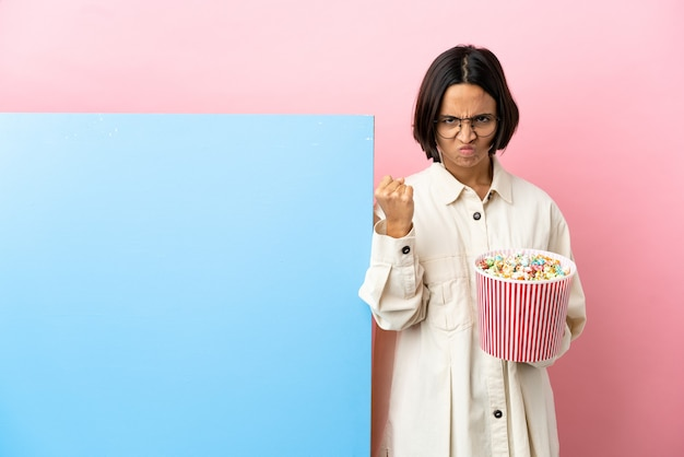 Young mixed race woman holding popcorns with a big banner over isolated background with unhappy expression