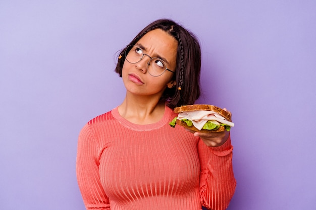 Young mixed race woman holding a sandwich isolated on purple background dreaming of achieving goals and purposes