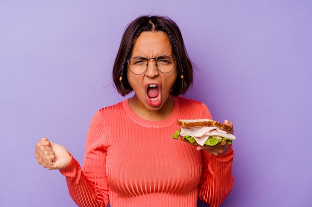 Young mixed race woman holding a sandwich isolated on purple background screaming very angry and aggressive.