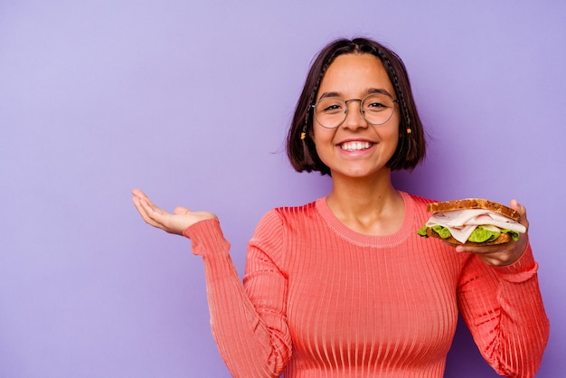 Young mixed race woman holding a sandwich isolated on purple background showing a copy space on a palm and holding another hand on waist.