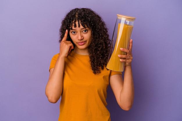 Молодая женщина смешанной расы, держащая спагетти, изолированные на фиолетовом фоне, указывая храм пальцем, думая, сосредоточилась на задаче.