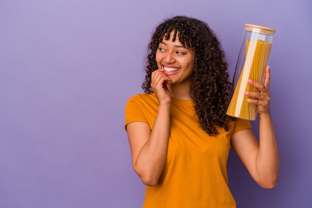 紫色の背景に分離されたスパゲッティを保持している若い混血の女性は、コピースペースを見ている何かについて考えてリラックスしました。