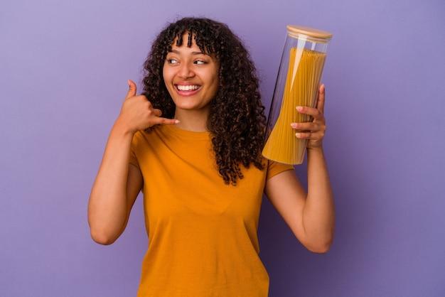 손가락으로 휴대 전화 제스처를 보여주는 보라색 벽에 고립 된 스파게티를 들고 젊은 혼합 된 인종 여자.