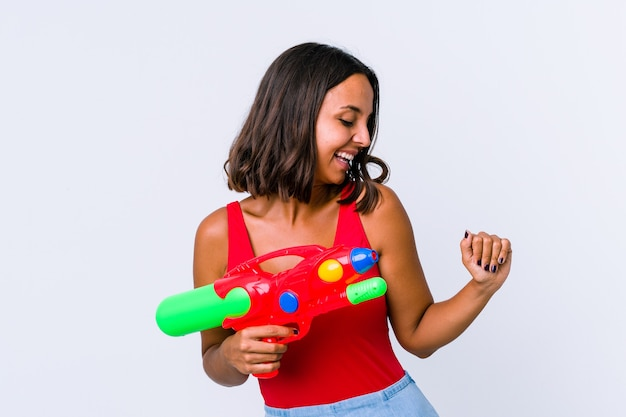 Young mixed race woman holding a water gun isolated dancing and having fun.