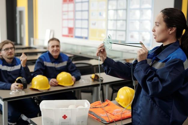 労働安全衛生指導中に酸素マスクを使用する方法を労働者に示すワークジャケットの若い混血の女性