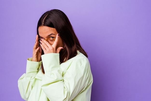 고립 된 젊은 혼합 된 인종 여자는 두려워 하 고 긴장하는 손가락을 통해 깜박입니다.