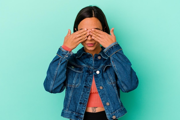 Young mixed race woman isolated on blue afraid covering eyes with hands.