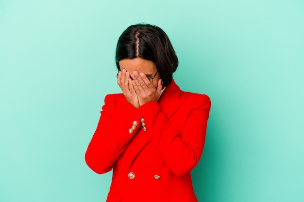 Young mixed race woman isolated on blue background afraid covering eyes with hands.