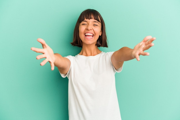 Young mixed race woman isolated on blue background feels confident giving a hug to the camera.