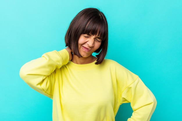 Young mixed race woman isolated on blue background having a neck pain due to stress, massaging and touching it with hand.