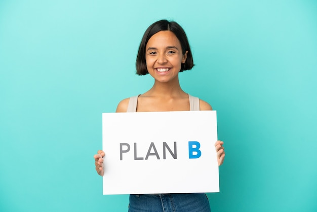 Young mixed race woman isolated on blue background holding a placard with the message plan b with happy expression