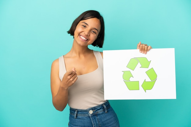 Young mixed race woman isolated on blue background holding a placard with recycle icon and pointing to the front