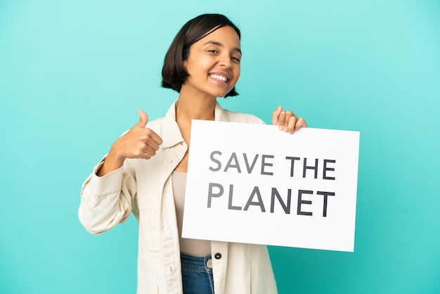 Young mixed race woman isolated on blue background holding a placard with text save the planet with thumb up