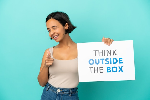 Young mixed race woman isolated on blue background holding a placard with text think outside the box and pointing to the front