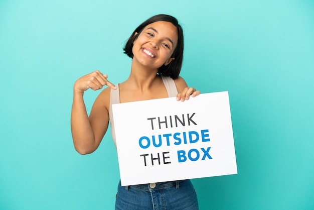 Young mixed race woman isolated on blue background holding a placard with text think outside the box and  pointing it