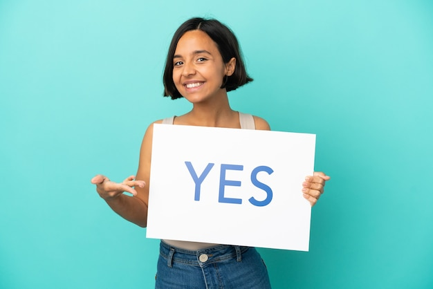 Young mixed race woman isolated on blue background holding a placard with text yes and pointing it