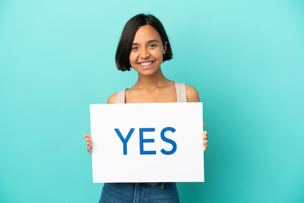 Young mixed race woman isolated on blue background holding a placard with text yes with happy expression