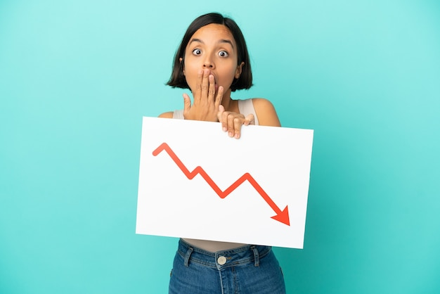 Young mixed race woman isolated on blue background holding a sign with a decreasing statistics arrow symbol with surprised expression