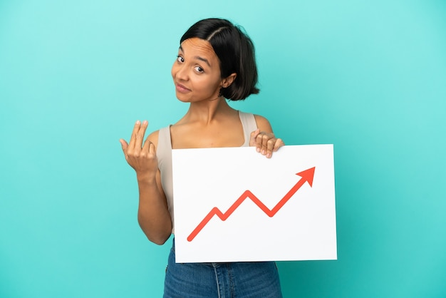 Young mixed race woman isolated on blue background holding a sign with a growing statistics arrow symbol and doing coming gesture