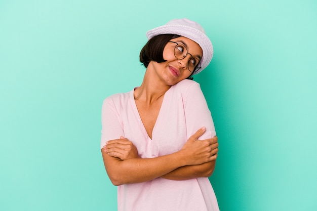 Young mixed race woman isolated on blue background hugs, smiling carefree and happy. Premium Photo