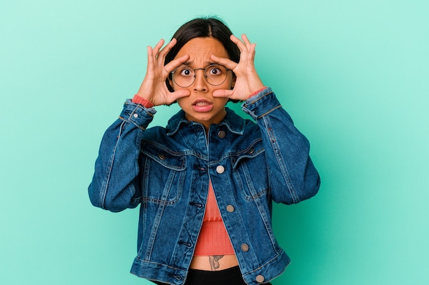 Young mixed race woman isolated on blue background keeping eyes opened to find a success opportunity.