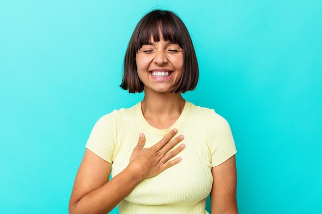 Young mixed race woman isolated on blue background laughs out loudly keeping hand on chest.
