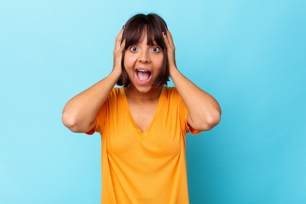 Young mixed race woman isolated on blue background screaming, very excited, passionate, satisfied with something.