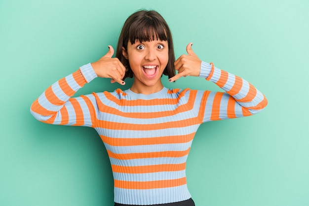 Young mixed race woman isolated on blue background showing a mobile phone call gesture with fingers.