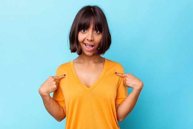 Young mixed race woman isolated on blue background surprised pointing with finger, smiling broadly.