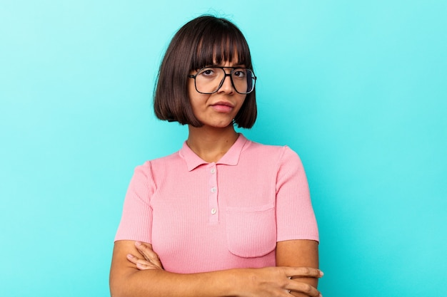 Young mixed race woman isolated on blue background suspicious, uncertain, examining you.