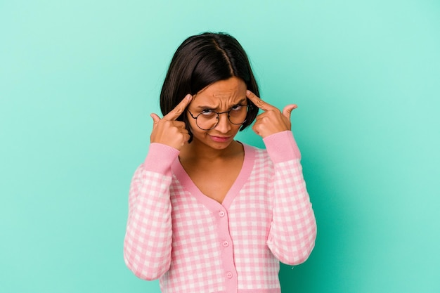 Young mixed race woman isolated on blue focused on a task, keeping forefingers pointing head.