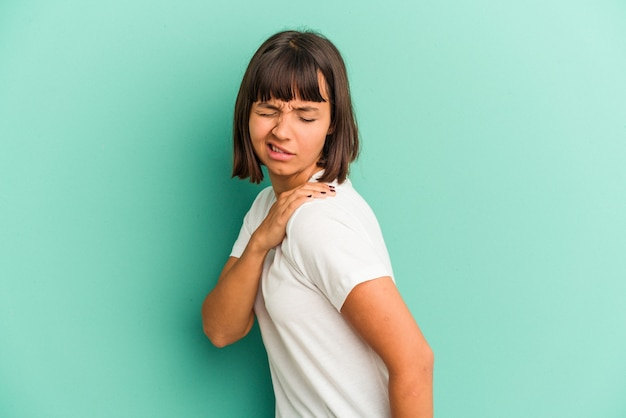 Young mixed race woman isolated on blue having a shoulder pain.