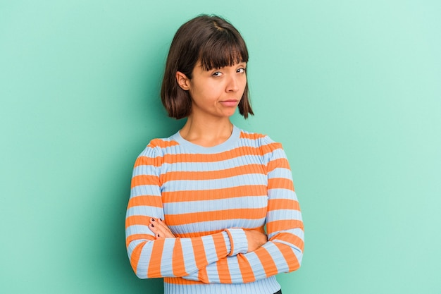 Young mixed race woman isolated on blue unhappy looking in camera with sarcastic expression.