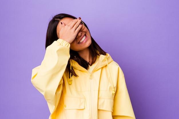 孤立した若い混血の女性は手で目を覆い、驚きを広く待っている笑顔。