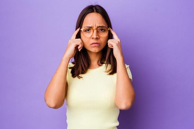 Изолированная молодая женщина смешанной расы сосредоточилась на задаче, держа указательные пальцы, указывая головой.