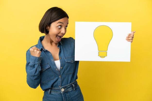 Молодая женщина смешанной расы изолирована, держа плакат со значком лампочки и празднует победу
