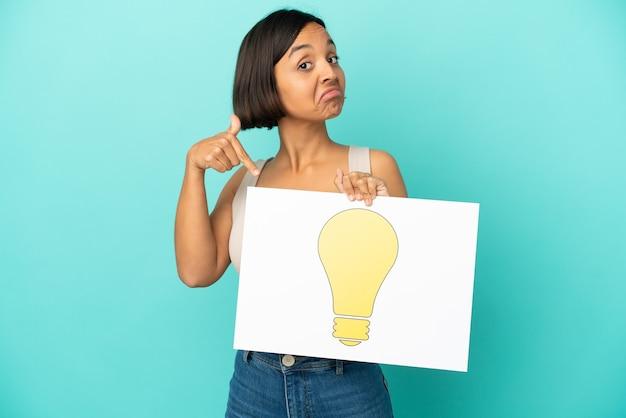 Молодая женщина смешанной расы изолирована, держа плакат со значком лампочки и указывая на него