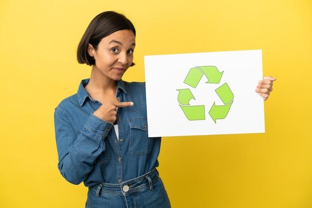 Молодая женщина смешанной расы изолирована, держа плакат со значком корзины и указывая на него