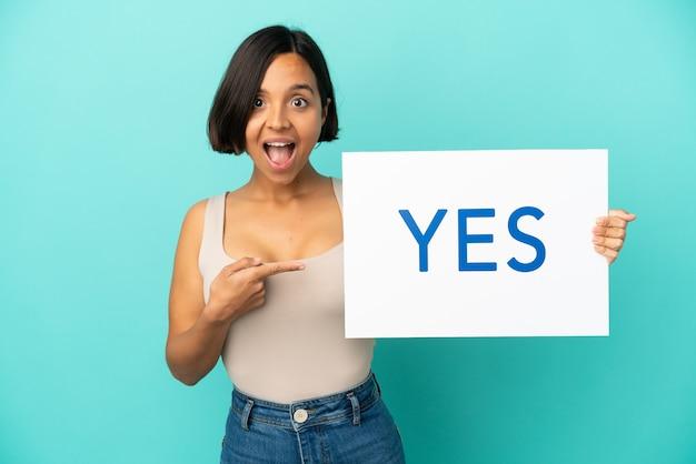 若い混血の女性が「はい」と書かれたプラカードを持ち、それを指している