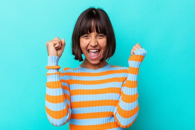 勝利、情熱、熱意、幸せな表情を祝う青い背景に分離された若い混血女性。