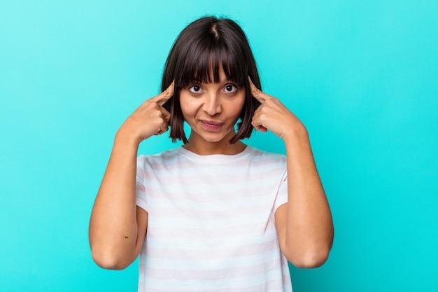 Молодая женщина смешанной расы, изолированная на синем фоне, сосредоточилась на задаче, держа указательные пальцы, указывая головой.