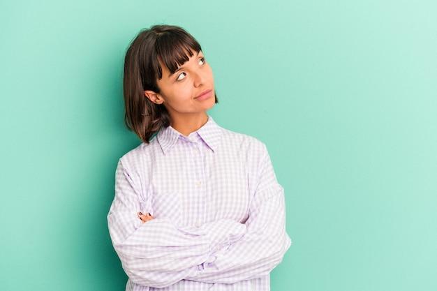 舌を突き出して面白いとフレンドリーな青い背景に分離された若い混血女性。