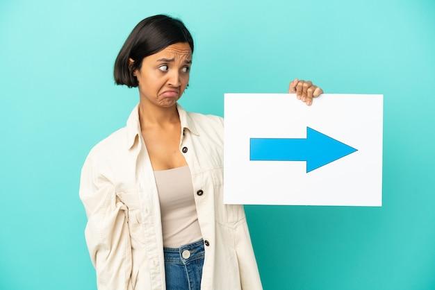 矢印記号のプラカードを保持している青い背景で隔離の若い混血の女性