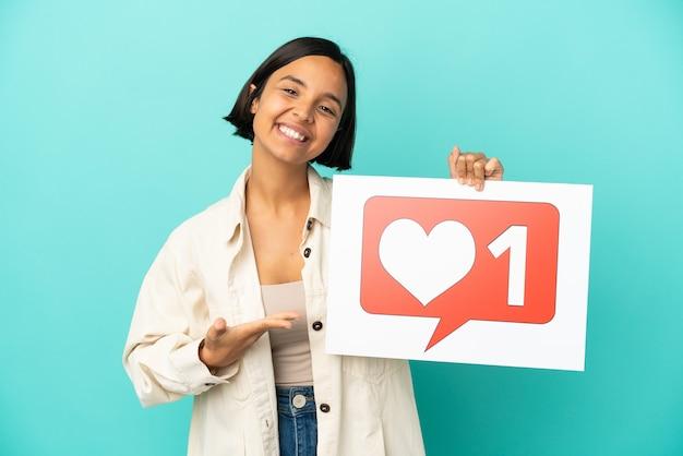 Молодая женщина смешанной расы изолирована на синем фоне, держа плакат со значком `` нравится '' и указывая на него Premium Фотографии