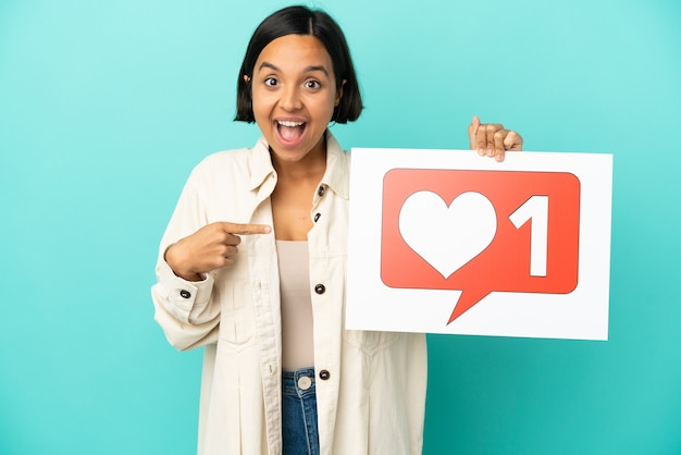Молодая женщина смешанной расы изолирована на синем фоне, держа плакат со значком `` нравится '' и указывая на него