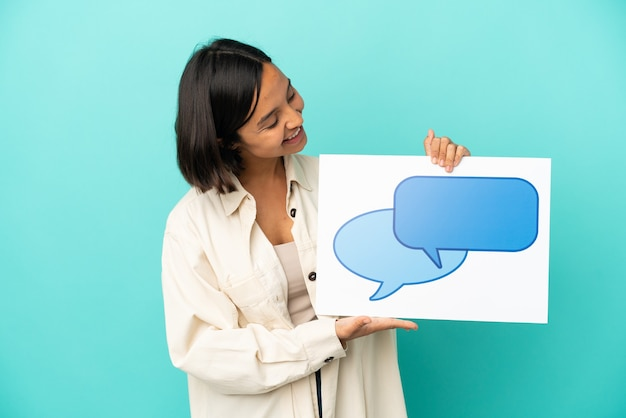 Молодая женщина смешанной расы изолирована на синем фоне, держа плакат со значком пузыря речи со счастливым выражением лица